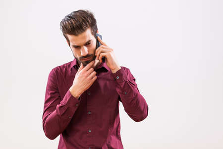 Studio shot portrait of young businessman who is talking on phone.