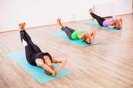 Three girls practicing yoga, Matsyasana  Fish pose 版權商用圖片