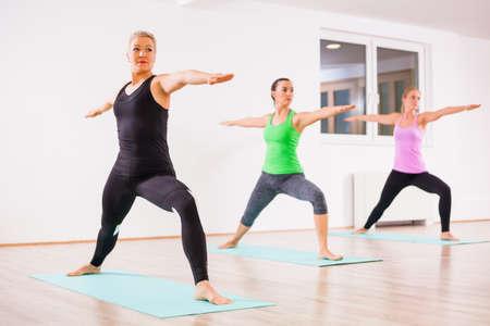 Three girls practicing yoga, Virabhadrasana  Warrior 2 pose