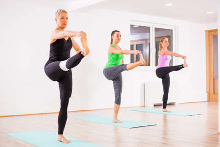 Three girls practicing yoga, Padangusthasana  Hand to big toe pose