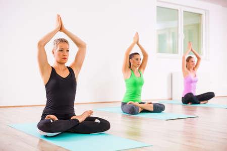 Three girls practicing yoga, Padmasana  Half lotus Position Stock Photo