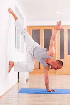 Adult man practicing indoor. Variation of yoga handstand pose. Vrksasana.