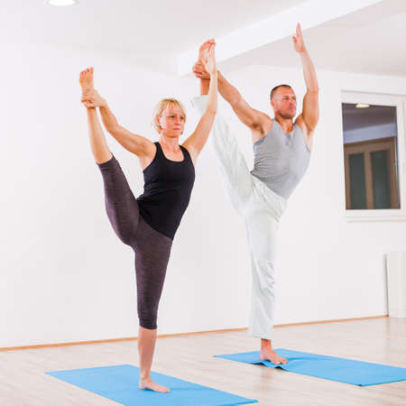 Adult man and woman practicing yoga, Padangusthasana  Extended Hand To Big Toe Pose Stock Photo