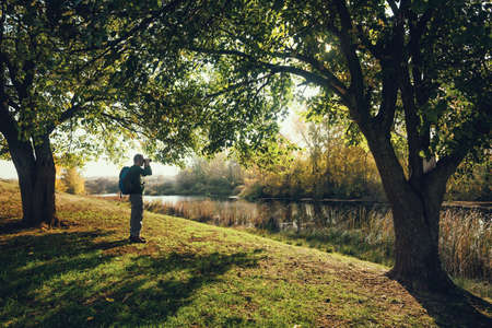 Man is watching birds with binoculars by the river in autumn. Stock Photo
