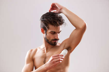 Young man is applying roll on antiperspirant to his armpit.