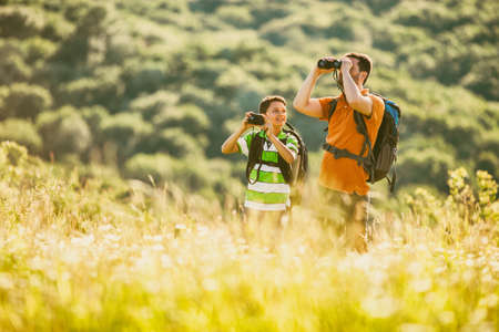 Father and son are hiking in nature in summer. Boy is photographing.