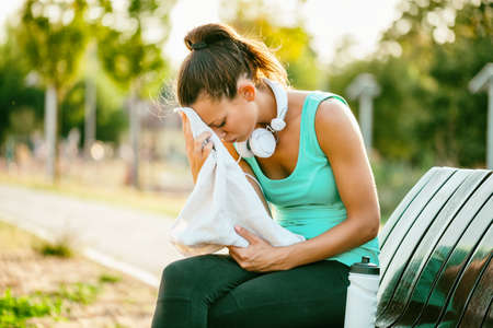 Young woman is relaxing after jogging on sunny day.