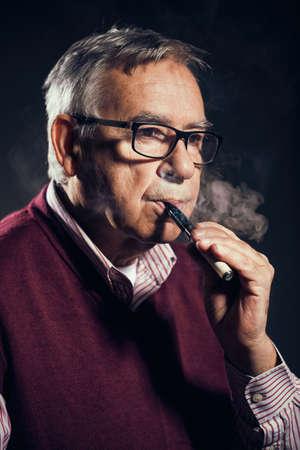 Portrait of senor man who is smoking electronic cigarette. Stock Photo