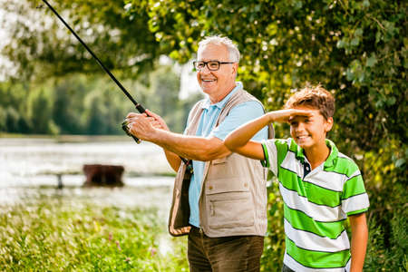 Grandfather and grandson are fishing on sunny day.