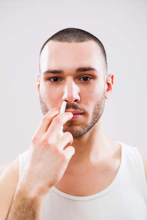 Young man is applying nose spray. Stock Photo