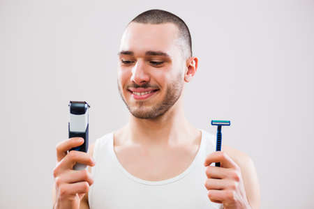 Young man is holding electric and classic razor. He is deciding which one to use to shave his beard.