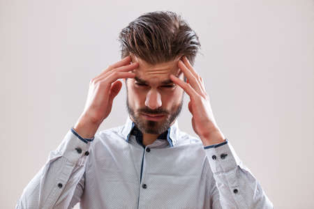 Portrait of stressed businessman who is having headache. Stock Photo