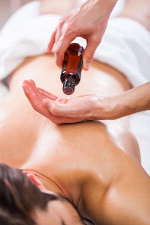 Young man is enjoying massage on spa treatment. Imagens