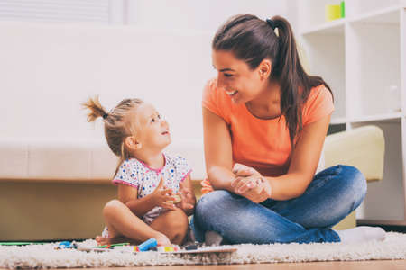 Mother and daughter in their home. They are playing with childs play clay.