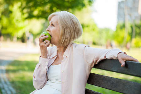 Adult woman sitting in park and eating apple.