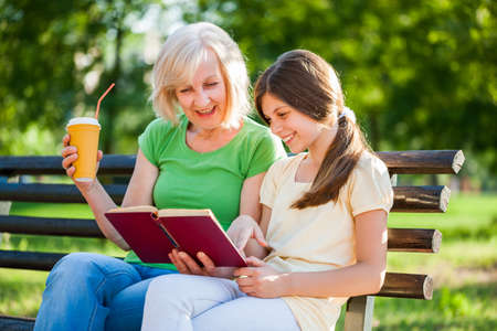 Grandmother and granddaughter are sitting in park and reading book. Stock Photo