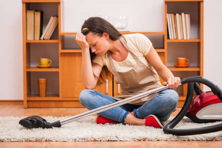 Young woman has to clean the house. She is bored and lazy.