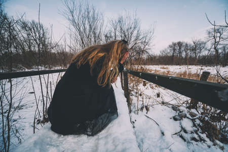 Depressed and lonely woman crying in forest in winter.
