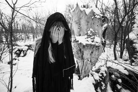 Depressed and lonely woman covering her face in forest in winter.