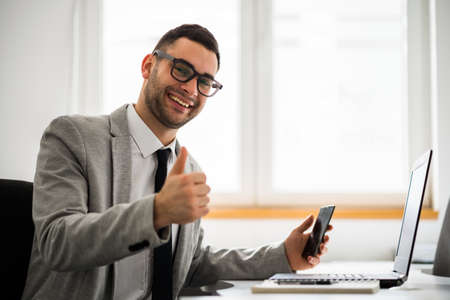 Young happy businessman is working in office.
