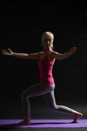 Woman exercising pilates. Standing lunge with arm rotation.