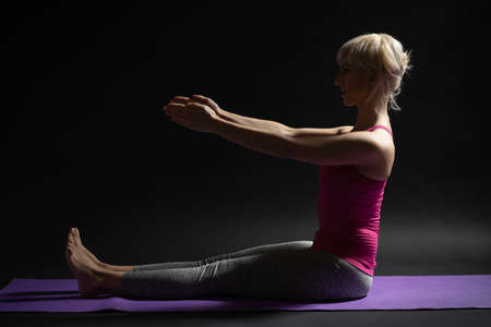 Woman exercising pilates. Spine stretch forward exercise. 写真素材 - 119544264