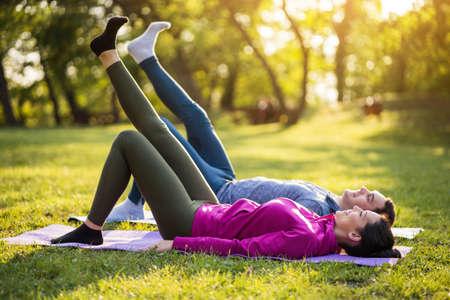 La pareja está haciendo ejercicio en el parque. Ejercicio para la recuperación de la ciática.