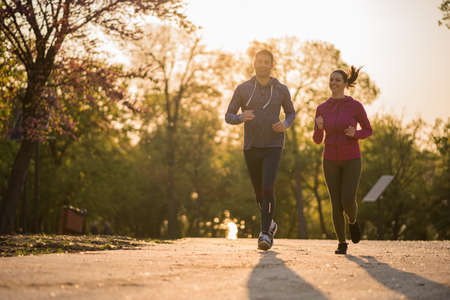 Happy couple is jogging in park. Stock Photo