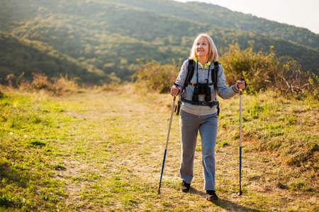 Senior woman is hiking in mountain. Active retirement. Stockfoto