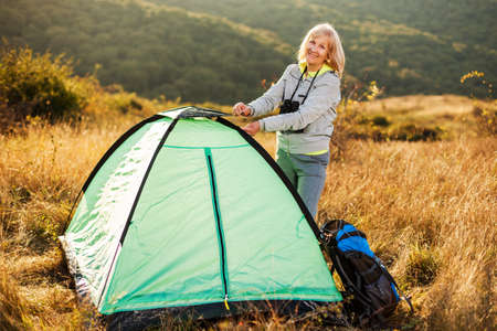 Senior woman is camping in mountain. Active retirement. Stock Photo
