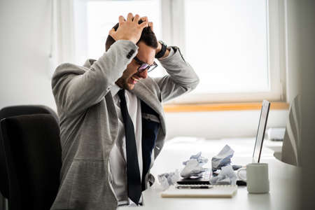 Young businessman is angry and frustrated. Imagens