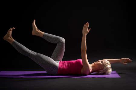 Vrouw die pilates uitoefent. Oefening voor de gezondheid van het lichaam.