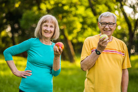 Happy senior couple is eating apples exercising in park. 免版税图像