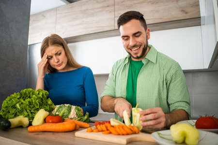 Wife does not like when her husband is cooking. Stock Photo