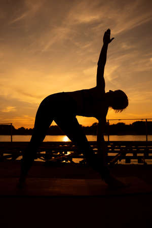 Woman practicing yoga in sunset. Trikonasana, Bikram triangle right