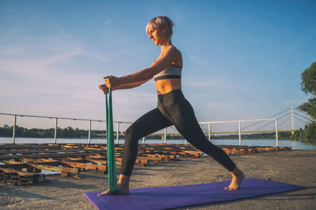 Woman exercising pilates with elastic band on sunny day.