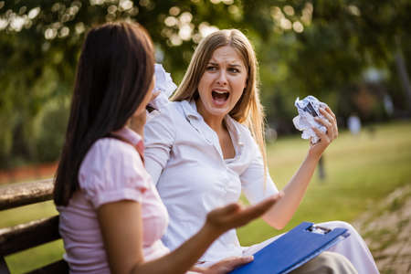 Business colleagues are arguing in park on break. Stock Photo