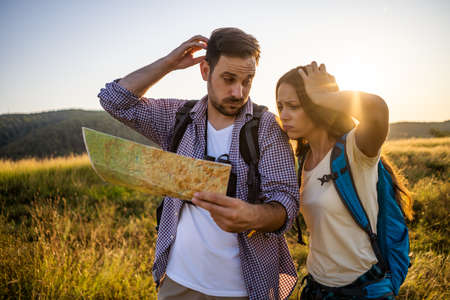 Couple is hiking in mountain. They are looking at map.