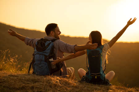 Young happy couple is hiking in monutain and enjoying sunset.