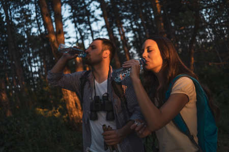 Young couple is hiking in forest. They are drinking water.