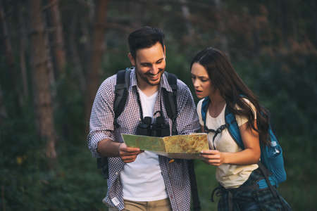 Happy couple is hiking in forest. They are looking at map. 版權商用圖片