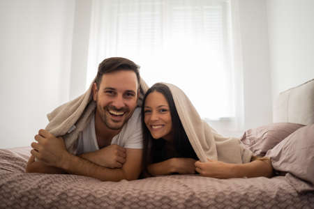 Happy couple is having fun in bed. Stock Photo