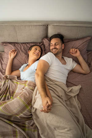 Young couple is resting in bed after work. Stock Photo