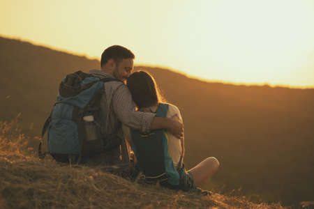 Young happy couple is hiking in mountain and enjoying sunset. Stock Photo