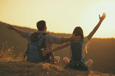 Young happy couple is hiking in mountain and looking at sunset. Stock Photo