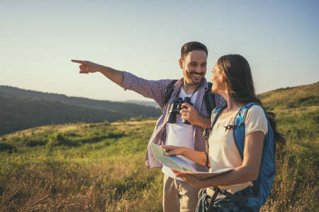 Happy couple is hiking in mountain. They are looking at map. Stock Photo