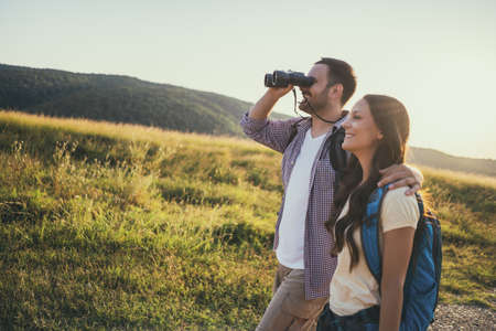 Happy couple is hiking in mountain. They are watching nature with binoculars. Stock Photo