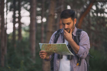 Adult man is hiking in forest. He is looking at map.