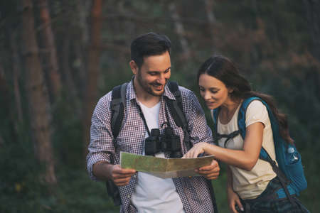 Happy couple is hiking in forest. They are looking at map. Фото со стока