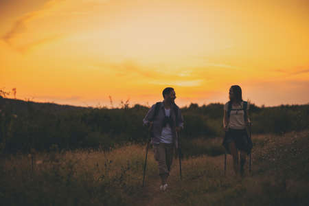 Young couple is hiking in mountain in sunset. Фото со стока